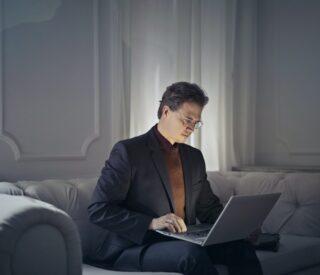 Mand arbejder på computer i jakkesæt