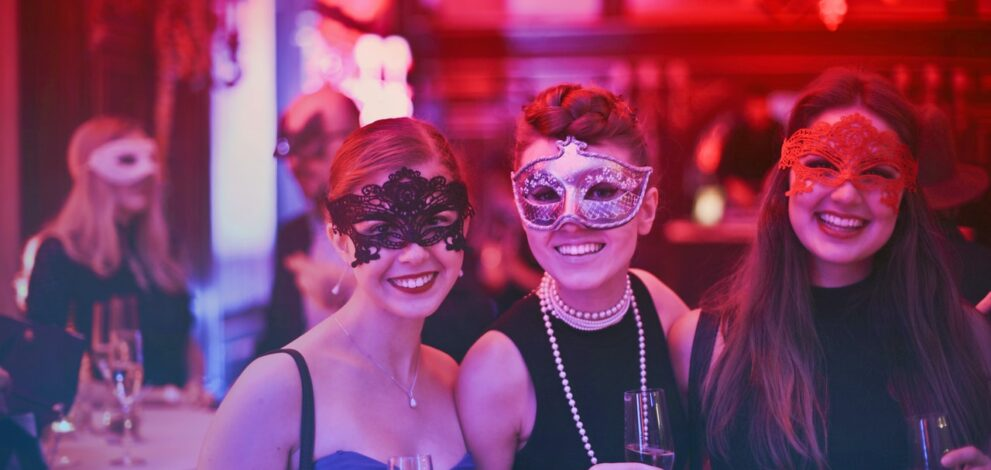 Tre kvinder har masker på til kostumefest
